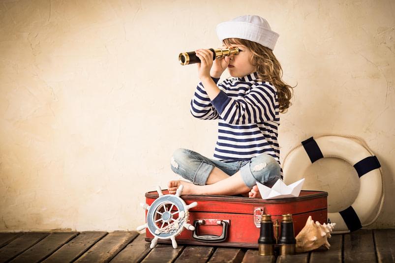 Als Matrosin verkleidetes Mädchen sitzt auf einem Koffer und guckt in ein Fernrohr